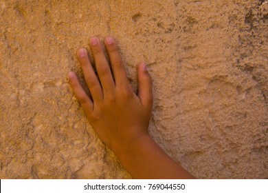 child hand on the old weathered wall of limestone