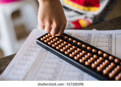 child hand over math problem counting abacus