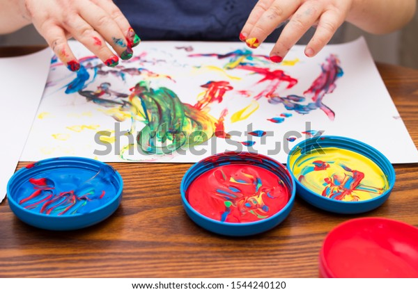 child hand painting on wooden table with color paints
