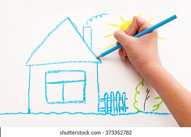 A child hand with pencil is drawing picture of country house