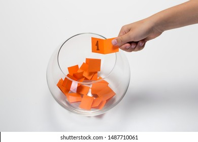 Child hand picking ticket with number one from a glass bowl, random name ballot, simple raffle