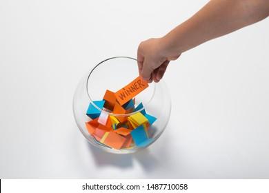 Child hand picking winner from a glass bowl, random name ballot, simple raffle