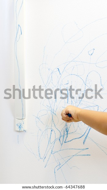 child hand scribbling with blue crayon on white refrigerator door