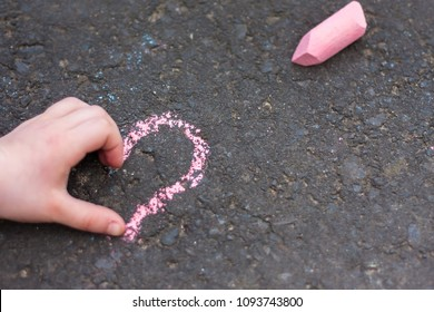 Child hand shows heart sign on chalk drawing