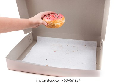 Child hand stealing the last donut from the box