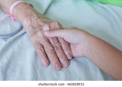 Child hand touches and holds an old woman in hospital.