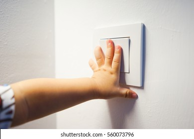Child hand turning on the light with a wall switch