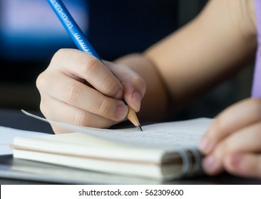 Child hand is using pencil to practice writing on a book. Kid learning to write letter on to a paper, For pre school education concept.