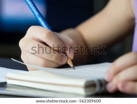 Child hand is using pencil to practice writing on a book.
