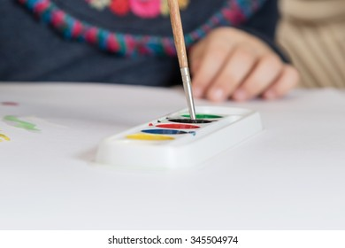 Child hand wets the brush in black watercolor closeup with focus on brush with a blurred background
