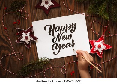 Child hand writes happy new year on sheet on wooden background, the concept of holiday and lettering. Frame made of handmade felt toys, rustic style, toning