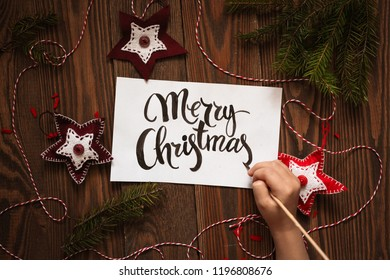 Child hand writes Merry Christmas on a sheet on a wooden background, concept of holiday and lettering. Frame made of handmade felt toys, rustic style, toning