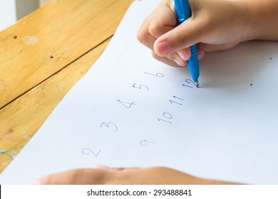 Child hand writing letters with blue pen