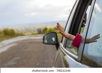 Child hands in a car window during travel to vacation