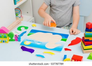 Child hands collect wooden puzzle