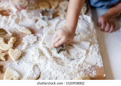 Child hands are cooking Christmas gingerbread cookies in home kitchen. Kid is playing with dough and flour. Little girl preparation holiday homemade pastries. Children chef concept.