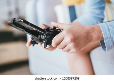 Child hands with game controller connected with smartphone close up image. Electronic devices and technology concept