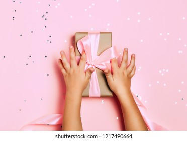 Child hands holding beautiful gift box on pink background, with sparkling glitter around. Holiday, bright and festive view, flat lay. Copy space for text. Christmas greeting banner.