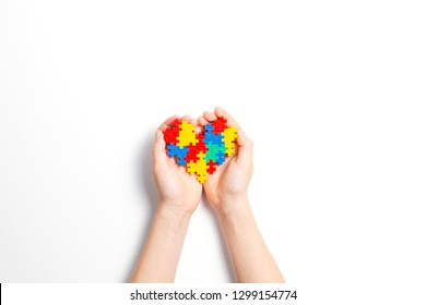 Child hands holding colorful heart on white background. World autism awareness day concept