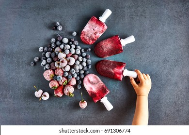 Child hands holding delicious home-made frozen popsicles of black currant. On a grey table, top view