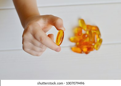 Child hands holding fish oil omega 3 gel capsula on white wooden background