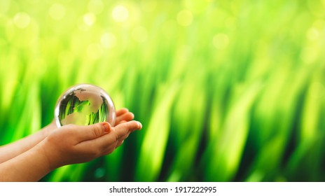 Child hands  holding glass green planet. Save Earth. Concept of the Environment World Earth Day