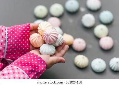 Child hands holding meringues on grey background
