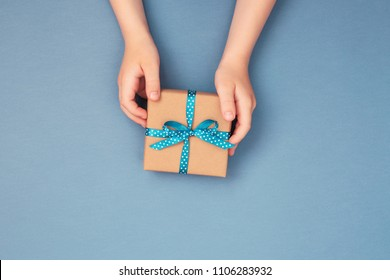 Child hands holding one gift box wrapped in kraft paper tied with blue ribbon in polka dots on blue grey background. Top view, place for text. Holiday concept.