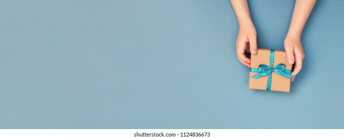 Child hands holding one gift box wrapped in kraft paper tied with blue ribbon in polka dots on blue grey background. Top view, place for text. Holiday concept, banner for site.