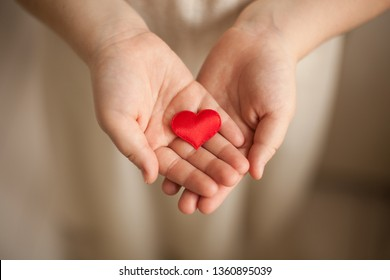 child hands holding red heart, health care, love and family concept, world heart day