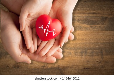 Child hands holding red heart          - Image