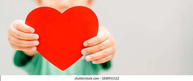 Child hands holding red heart for share Donate.Health care pediatric.family insurance.World heart day, world health day,CSR responsibility, Adoption foster kids.Worship with faith.Banner background.