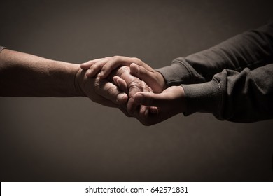 Child hands holding senior woman's hands on brown background