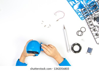 Child hands making blue robot. Robotic, learning, technology, stem education for children background