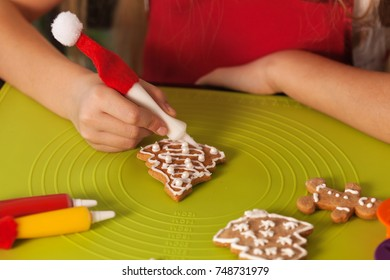 Child hands making christmas cookies, decorating a gingerbread xmas tree with white icing - closeup, shallow depth