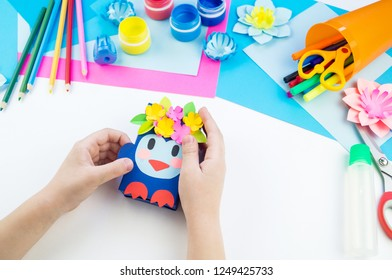 Child hands making a penguin out of paper. Application of children's creativity. Kindergarten and craft school. White background and materials for crafts.