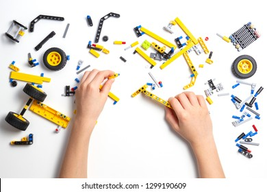 Child hands making robot car. Robotic, learning, technology, stem education for children background