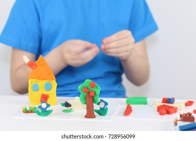 Child hands molding bright house, sheep, flowers from plasticine on table in room