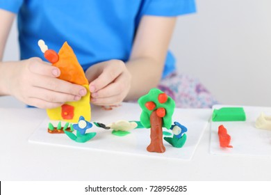 Child hands molding house, tree, flowers from plasticine on table in room