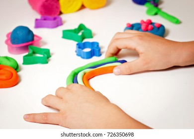 Child hands molding modeling clay or plasticine on white table