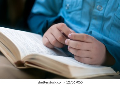 Child hands are on the open book