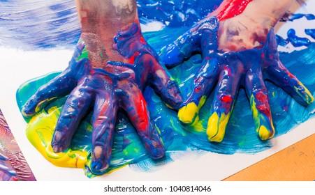 Kinderhände in bunten Farben gestrichen. Bildungs-, Schule-, Kreativitäts- und Malkonzept. Weicher Fokus und unscharfer