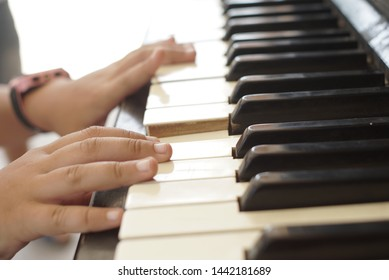 child hands play the old piano
