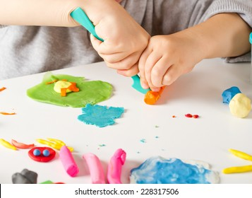 Child hands playing with colorful clay