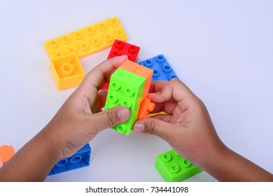A child hands playing with colorful toy blocks.