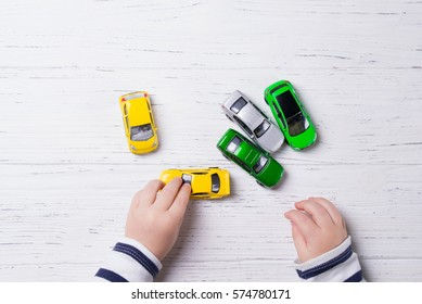 Child hands playing with miniature toy cars, wooden background, top view