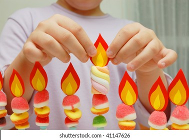 child hands putting a paper flame on handmade hanukah menorah isolated on white