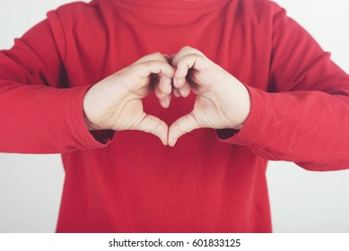child hands showing sign of heart