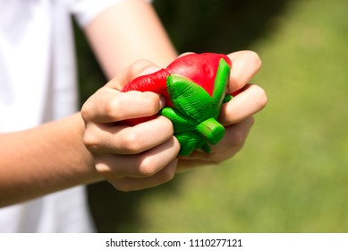 Child hands squeezing a red strawberry squishy toy