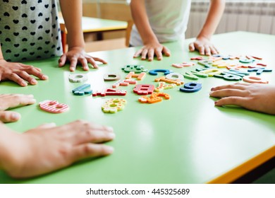 Child hands with wooden toy plate alphabet in classroom